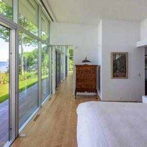 W sypialni również zamontowano duże przeszklenia. W białym wnętrzu dobrze wyeksponowano szafkę (w starym stylu) i obraz. Fot. Paul Warchol