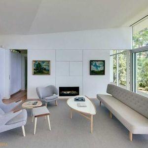 W salonie wokół kominka ustawiono prostą sofę i kilka foteli. To idealne miejsce na spotkania rodzinne i relaks w chłodne wieczory. Fot. Paul Warchol