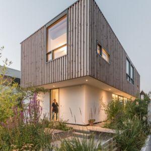 Bryła domu została rzeczywiście zaprojektowana w postaci dwóch bloków ułożonych jeden na drugim. Elewacja górnego elementu domu została obłożona drewnianymi deskami. Fot. GAAGA