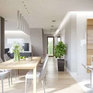 Drewniany stół w jadalni i drewniane  fronty mebli kuchennych ocieplają to jasne wnętrze. Fot. HomeKONCEPT