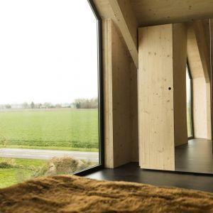Odsłonięta drewniana konstrukcja nadała charakterystyczną, ciepłą lecz surową atmosferę wnętrzom domu. Fot. Koen Broos
