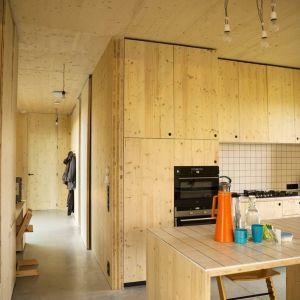 Wszystkie meble także są niestandardowe i oryginalne (biurko biurowe, ławki, podkłady, kominek, kuchnia itd.), a wykonane zostały z tego samego materiału, co konstrukcja domu, dopełniając kompletnie drewniane wnętrza. Fot. Koen Broos