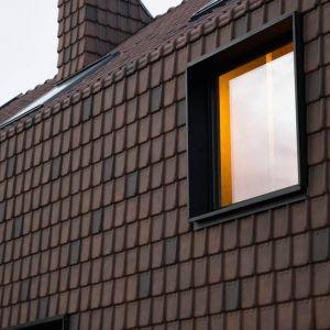 Jednolity kształt elewacji przerywają kwadratowe okna zamontowane w trzech różnych rozmiarach. Fot. Koen Broos