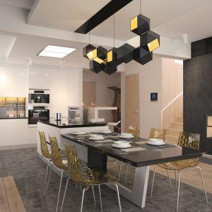 Jadalnia została zaprojektowana niezwykle nowocześnie. Stół połączono tu w jednym ciągu z barem śniadaniowym, a którym ukrywa się część przestrzeni roboczej kuchni. Wyjątkowymi elementami aranżacji są tu nowoczesne krzesła i elementy oświetlenia, które są dekoracją samą w sobie. Fot. Archetyp