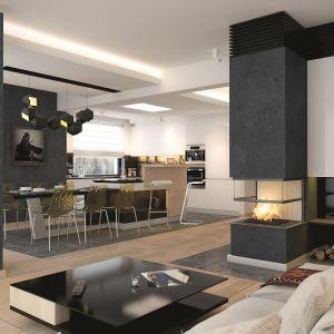 Salon, jadalni i kuchnia zaprojektowano w formie open space'u. Na uwagę zasługuje ciemne wykończenie ściany kominkowej, ściany w jadalni i strefy za telewizorem. Czerń doskonale współgra z jasnymi meblami i drewnem na słomkowym drewnem na podłodze. Fot. Archetyp