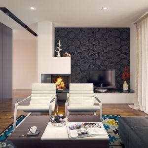 Ścianka telewizyjna z modną tapetą, jak również nowoczesny kominek decydują o przytulności wnętrza. Meble i modny dywan z barwami turkusu i ochry dodają całości wyjątkowo eleganckiego charakteru. Fot. Archetyp