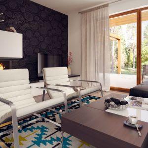 Salon urządzony jest bardzo nowocześnie, ale zarazem przytulnie. Biel i drewno z nutą metalu dobrze komponuje się z kolorem stolika kawowego i nowoczesnymi meblami wypoczynkowymi. Fot. Archetyp