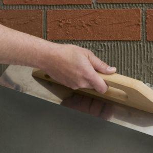 Pierwszym krokiem jest rozprowadzenie kleju Elastolith pacą na powierzchnię ok. 1 mkw. Grubość warstwy powinna wynosić 2 mm. Fot. Elastolith