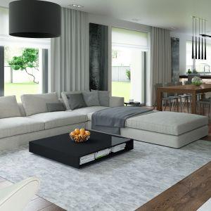 W salonie główne miejsce zajmuje narożna kanapa i niewielki, nowoczesny stolik. Fot. HomeKoncept