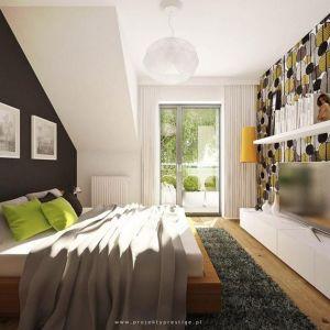 Skosy na poddaszu umożliwiają ciekawą aranżację sypialni. W tym wnętrzu zdecydowano się na ożywienie wnętrza zmieniając kolory dwóch ścian. Na ciemnej ścianie za łóżkiem dobrze prezentują się pamiątkowe zdjęcia. Fot. Presige