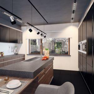 Kuchnia z modną wyspą i ciemną zabudową meblową zaprojektowano bardzo funkcjonalnie. Kamienny blat zapewni komfort pracy. Z kolei duże okno gwarantuje duży dopływ światła dziennego do tej przestrzeni. Fot. Archetyp