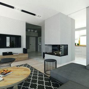 Nowoczesne wformie – czarny stolik kawowy ipuf – doskonale kontrastują zelementami drewna. Czarny dywan zbiałym wzorem iciekawe lampy pięknie uzupełniają całość. Fot. MTM Styl