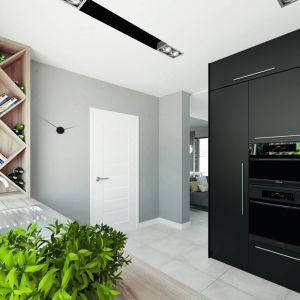 Kuchnia została odseparowana od salonu ścianą zkominkiem. To wnętrze jest zgranym duetem czerni ibieli. Fot. MTM Styl