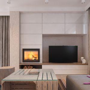 W salonie interesującym elementem jest ściana kominkowa obudowana białymi płytkami na wysoki połysk. Fot. MTM Styl