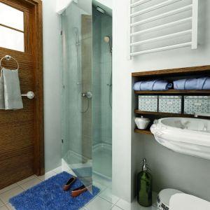 Biała łazienka została zaplanowana bardzo funkcjonalnie. Ocieplono ją drewnem i turkusowymi dodatkami. Fot. Archeco