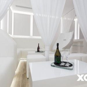 Przestrzeń wypełniona jest białymi pufami, stolikami i kanapami. Wszechobecną biel przełamuje czarny bar ze ścianą z lacobelu oraz kontuarem pokrytym płytkami Bisazza Frozen Garden. Fot. Naboo