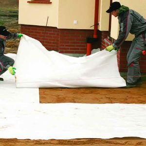 2 Kładziemy warstwę geowłókniny. Układamy ją na zakładkę o szerokości około 15–20 cm. Warto pamiętać o zrobieniu kołnierza z geowłókniny, który zabezpieczy ścianę. Fot. Libet