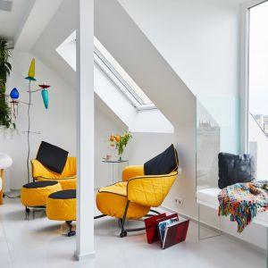 """Żółte fotele rodem z lat 80-tych, czy fikuśna, """"zakręcona"""" półka na książki stanowią swoistą """"kolorową wisienkę"""" na kremowym białym torcie """"wnętrz"""". Fot. Erdőháti Áron"""