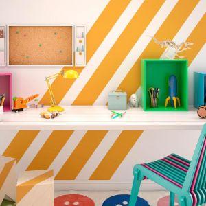 Geometryczne wzory ze szkolnego zeszytu warto przenieść wprost na ścianę. Pomalowane na nasycone odcienie jak np. energetyczny żółty będą nie tylko zdobić dziecięcy pokój, ale także sprzyjać rozwojowi kreatywnego i nieszablonowego myślenia. Akcesoria w żywych tonacjach jako dekoracja biurka z pewnością zachęcą dziecko do zasiadania przy nim do lekcji.  Fot. Beckers