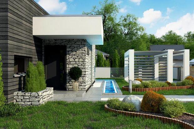 Prezentujemy nowoczesny dom parterowy, o surowej elewacji, gładkim białym tynku łączonym z kamieniem oraz ciemnym drewnem. Zastosowano ciemną stolarkę oraz elementy zacieniające.