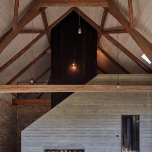 """Podkreślono oryginalną specyfikę każdego z tych dwóch budynków poprzez zachowanie rzeźbiarskiej objętości tradycyjnej, """"czarnej"""" kuchni w drewnianym domku i panoramiczny widok wychodzący z  bram kamiennej stodoły. Fot. Jakub Skokan, Martin Tůma  BoysPlayNice"""