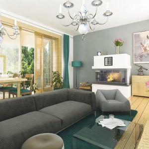 Przestronny salon połączony z jadalnią przesycony jest bielą i słomkowa barwą drewna. Całość dopełniają ciemnozielone dodatki. Fot. Dom dla Ciebie Pracownia  Projektowa Archeco