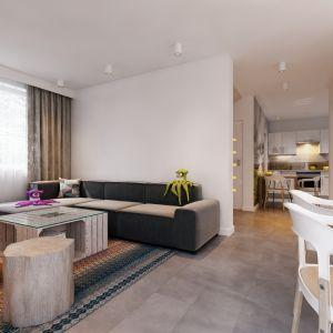 Na uwagę zasługują minimalistyczne meble – ciemnoszara kanapa, drewniany stół inspirowany stylistyką mebli z euro palet i siedzisko w postaci surowego pieńka. Fot. MTM Styl