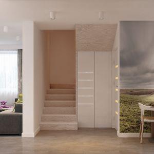 Strefy funkcjonalne w otwartej przestrzeni dziennej podkreśla ich różnorodne wykończenie. W salonie dominuje biel z nutą beżu, w holu znaczącym akcentem staje się drewno, a w jadalni dominującą dekoracją jest fototapeta na ścianie. Fot. MTM Styl
