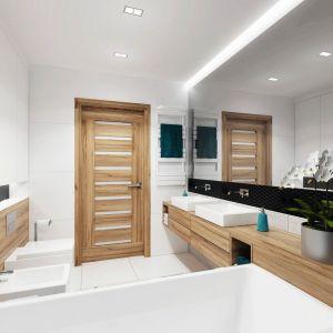Białe wnętrze łazienki ocieplają drewniane elementy. Fot. Domy w Stylu