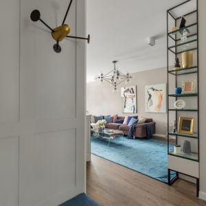 Stolik, który znajduje się przy sofie jest na tyle delikatny na tle dużego kobaltowego dywanu, że wtapia się w niego idealnie i jest praktycznie niezauważalny. Fot. Pion Poziom Fotografia Wnętrz