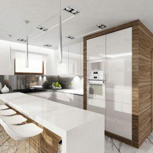 """Kuchnia jest tylko częściowo otwarta na jadalnię. Obie strefy rozdziela bar śniadaniowy z białym blatem i drewnianym wykończeniem. Biała zabudowa kuchenna na jednej ze ścian została """"zakuta w drewno"""", co doskonale koresponduje ze stylistyką salonu. Fot. Domy w Stylu"""