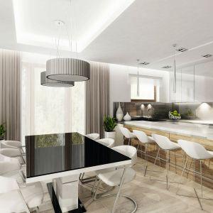 Jadalnię wypełnia światło, głównie dzięki dużym przeszkleniom. Całość spinają gustowne meble: biały stół z czarnym blatem oraz dodatki: lampy i zasłony. Fot. Domy w Stylu