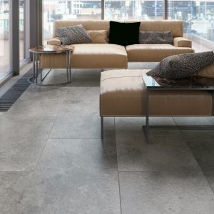 Osoby ceniące nieoczywiste rozwiązania aranżacyjne, mogą wybrać płytki imitujące kamień także do salonu. Ciekawy efekt wizualny osiągniemy, wykorzystując elementy o różnym odcieniu szarości, które na wybranej ścianie ułożymy w formie wielkoformatowych puzzli. Dzięki takiemu zabiegowi zdynamizujemy wystrój wnętrza, które nabierze oryginalnego a zarazem eleganckiego stylu. Fot. Cerrad