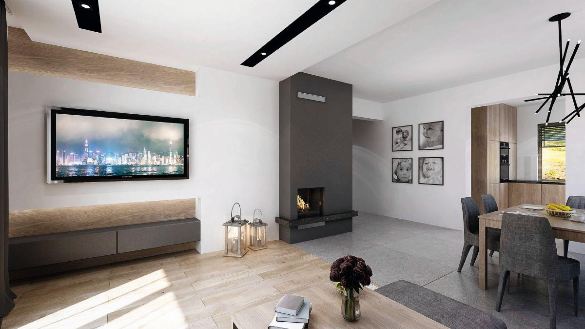 Reprezentacyjny salon zaprojektowano z dużym wyczuciem smaku. Duet bieli czerni uzupełniają ciemnoszare meble i drewno. Fot. Domy w Stylu