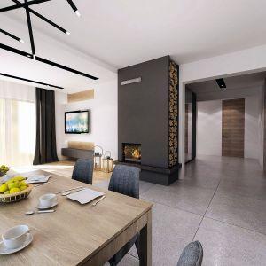 Ściana kominkowa została tak ulokowana, aby ciepłem domowego ogniska cieszyć się zarówno z salonu, jak też z jadalni. Fot. Domy w Stylu