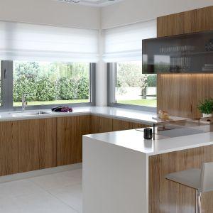 Kuchnię urządzono w nowoczesnym, jasnym stylu i ocieplono ją drewnem. Fot. HomeKONCEPT