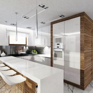 """Kuchnia jest tylko częściowo otwarta na jadalnię. Obie strefy rozdziela bar śniadaniowy z białym blatem i drewnianym wykończeniem. Biała zabudowa kuchenna na jednej ze ścian została """"zakuta w drewno"""", co doskonale koresponduje ze stylistyką salonu. Fot. MTM Styl"""