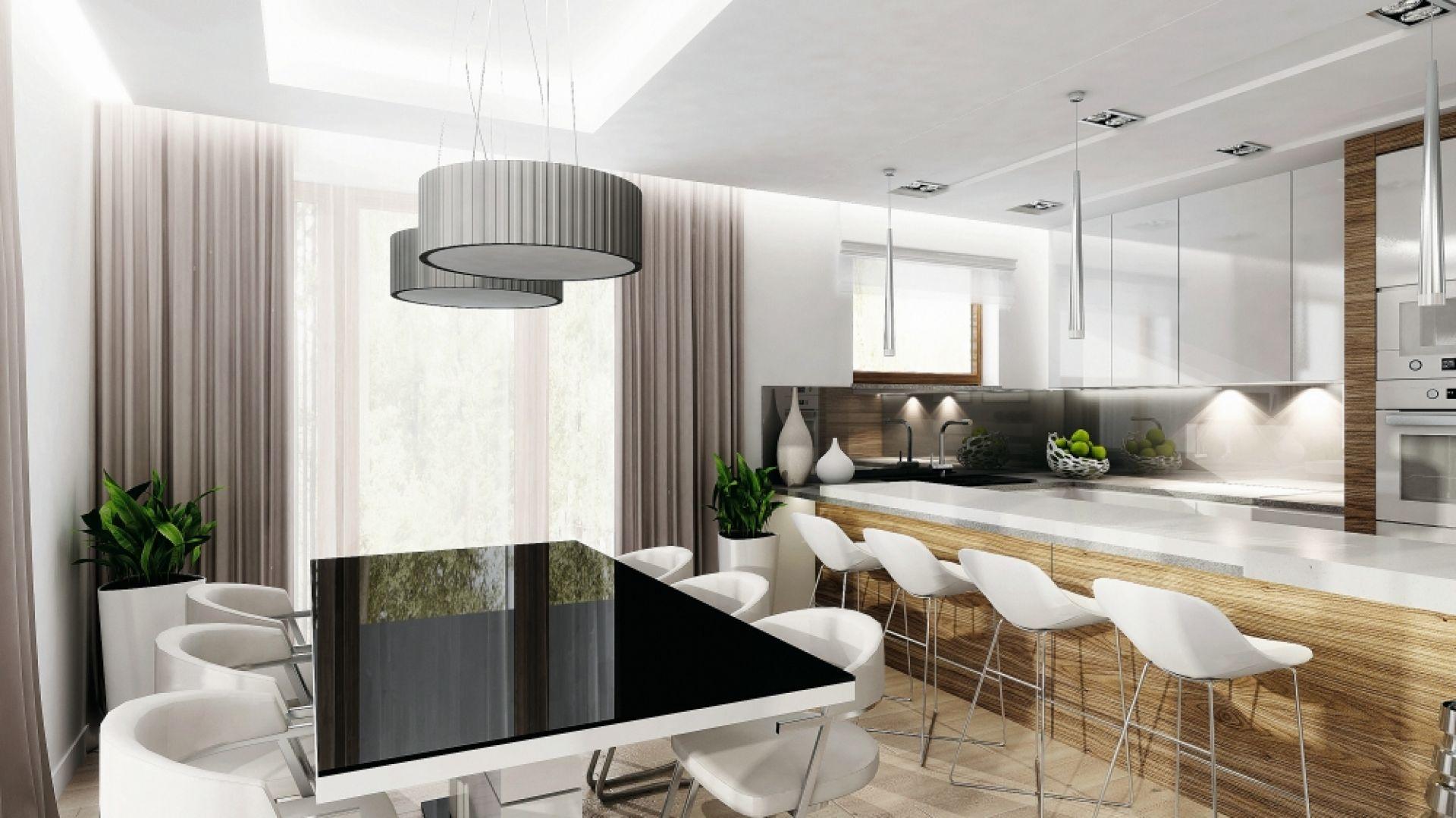 Jadalnię wypełnia światło, głównie dzięki dużym przeszkleniom. Białe ściany i meble jeszcze bardziej zwiększają efekt rozświetlenia tej części domu. Całość spinają gustowne meble: biały stół z czarnym blatem oraz dodatki: lampy i zasłony. Fot. MTM Styl