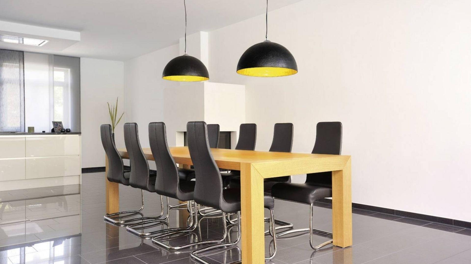 Wizualnie chłodne wnętrze, w kolorystyce biało-szarej, rozświetli ciepłymi barwami stołu i wnętrza lampa Forchini SLV©, która przykuwa uwagę. Fot. tomix.pl