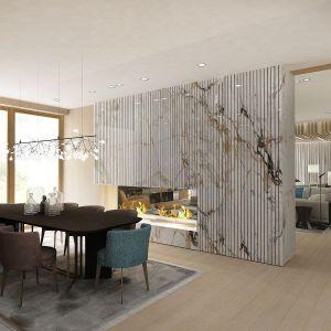 Część jadalna została oddzielona od salonu efektowną marmurową zabudową z biokominkiem. Fot. Wyrzykowski Studio