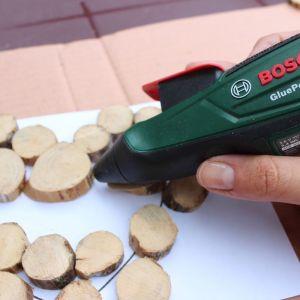 Krok 3 - Oszlifowane plastry drewna układamy na szablonie o kształcie serca, następnie łączymy ze sobą przy pomocy akumulatorowego pistoletu do klejenia Bosch GluePen. Fot. Bosch