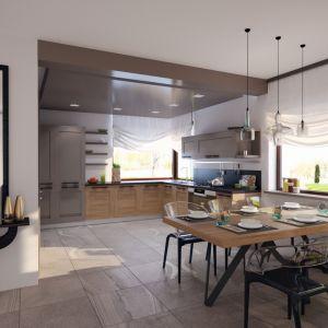 Jadalnia i kuchnia wyróżniają się dużym narożnym oknem w cienkiej ramie. Dzięki temu przestrzeń jest dobrze doświetlona. Ponadto, zastosowanie dużego lustra w sąsiadującym z jadalnią holu, optycznie powiększa całą przestrzeń. Projekt: Markus. Fot. Archetyp