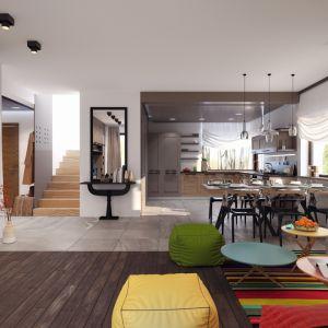 Otwarta przestrzeń została wypełniona nowoczesnymi meblami. Kolory dodatków dobrze komponują się z nowoczesnymi transparentnymi krzesłami w jadalni. Ozdobą tej przestrzeni są też nowoczesne lampy nad stołem. Projekt: Markus. Fot. Archetyp