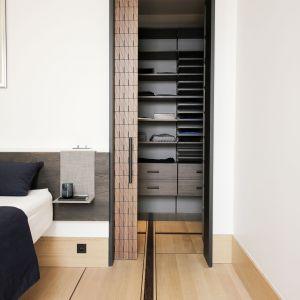Przestrzeń garderoby dostępna jest przez perforowane drzwi przesuwne, które przepuszczają światło.Fot. Romain Bourdais