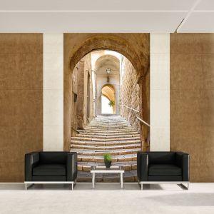 W nowoczesnym wnętrzu warto postawić na fototapetę, która ociepli pomieszczenie. Może ona przedstawiać schody w wąskiej uliczce spokojnego, starego miasta, na terenie południowej Europy czy Bliskiego Wschodu. Fot. Demural