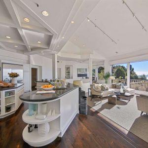 """Kuchnia z wyspą """"ocieplona"""" drewnianą podłogą. Fot. Open Homes"""