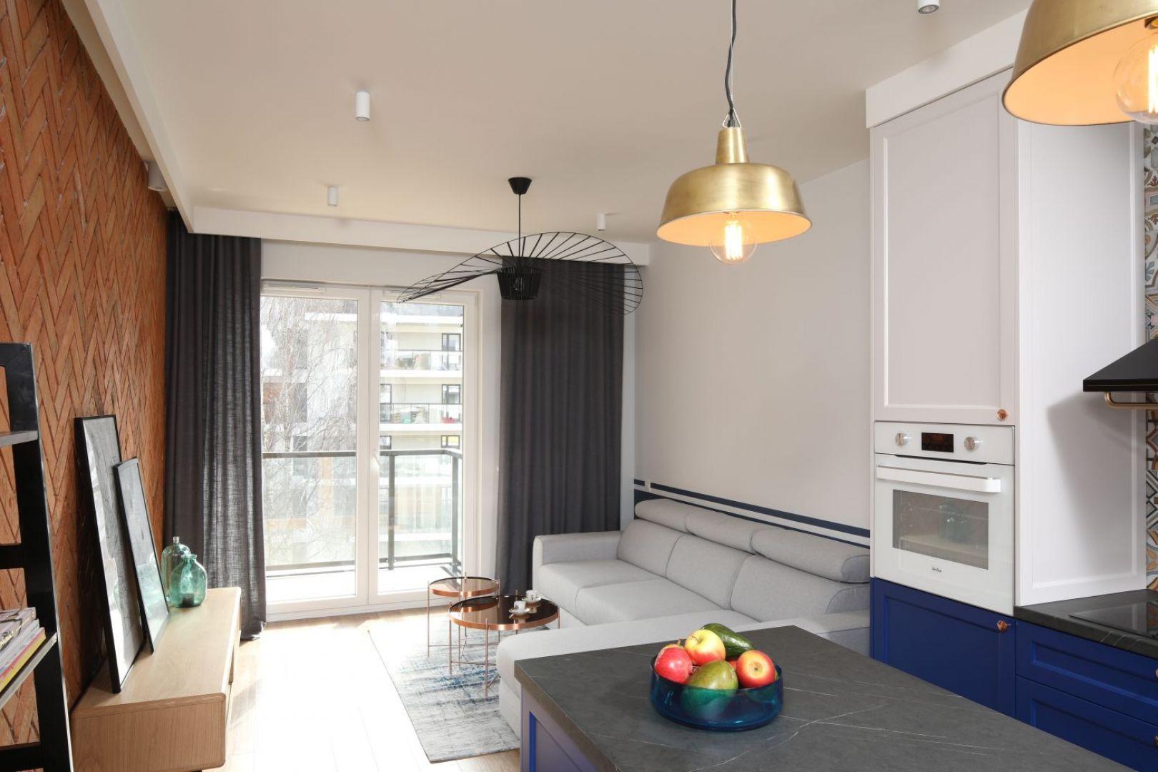 Salon otwierający się panoramicznymi oknami na taras czy balkon będzie wydawał się znacznie większy, przez zatracenie granicy pomiędzy wnętrzem domu a jego otoczeniem. Mały salon. Projekt: Anna Krzak. Fot. Bartosz Jarosz