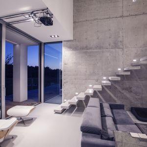Ten niewielki dom posiada przestronną - 5 m wys. strefę dzienną, której główną ozdobą jest ściana i schody wspornikowe wykonane z betonu architektonicznego. Fot. BXBstudio Bogusław Barnaś