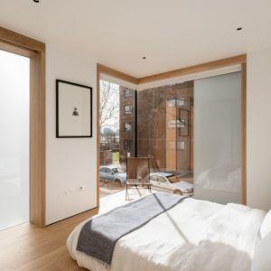 W sypialni dominuje biel. Ocieplono ją drewnianymi elementami wystroju. Projekt / Fot. Architect: Feilden Clegg Bradley Studios