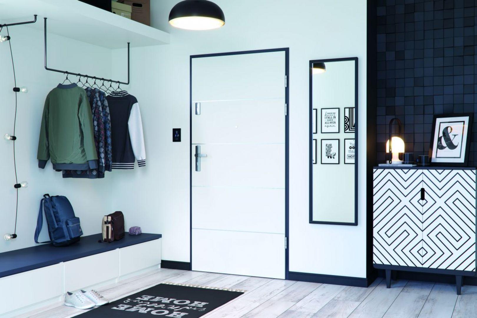 Drzwi wejściowe Kwarc w białym kolorze w oprawie z czarnej ościeżnicy dobrze wkomponują się w tło białej ściany, a srebrne intarsje na ich powierzchni wprowadzą do domu blask. Fot. Porta